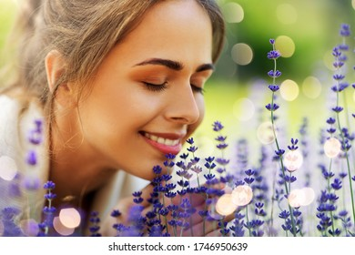 gardening and people concept - close up of happy young woman smelling lavender flowers at summer garden over festive lights background