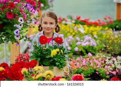 Gardening, planting - Lovely girl holding flowers in garden center.