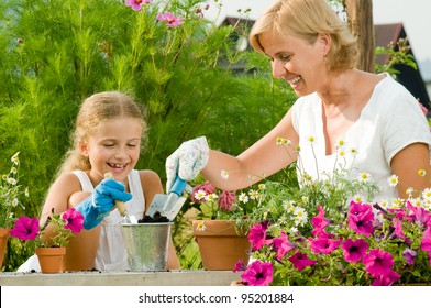 Gardening, planting - mother with daughter planting flowers into the flowerpot