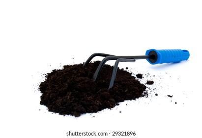 A gardening rake with potting compost on white