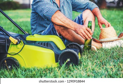 Gardening. Senior man take a rest in the yard and enjoying in beer after work with a lawn mower. Hobbies and leisure