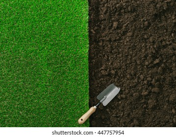 Gardening shovel on the fertile soil and grass, gardening and landscaping concept