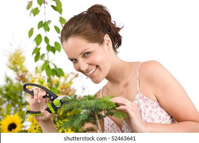 Gardening - Smiling woman cutting tree with pruning shears on white background