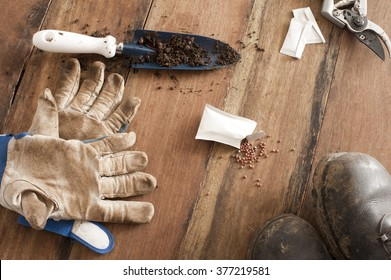 Gardening still life with gloves, a small trowel, open packet of spilled seeds, boots and secateurs for pruning on a wooden table