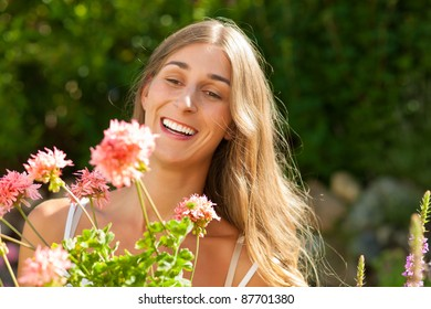 Gardening in summer - happy woman with flowers in her garden