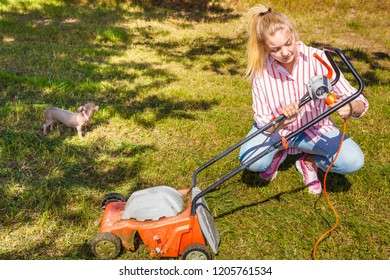 Gardening, taking care of house backyard, agricultural concept. Female person mowing green lawn with lawnmower in sunny day.