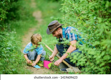 Gardening tools. Gardening hobby. Dad teaching little son care plants. Spring gardening routine. Planting flowers. Little helper in garden. Farm family. Little boy and father in nature background.