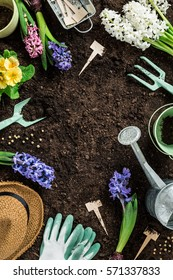 Gardening tools, hyacinth flowers, watering can and straw hat on soil background. Spring garden works concept. Layout with free text space captured from above (top view, flat lay).