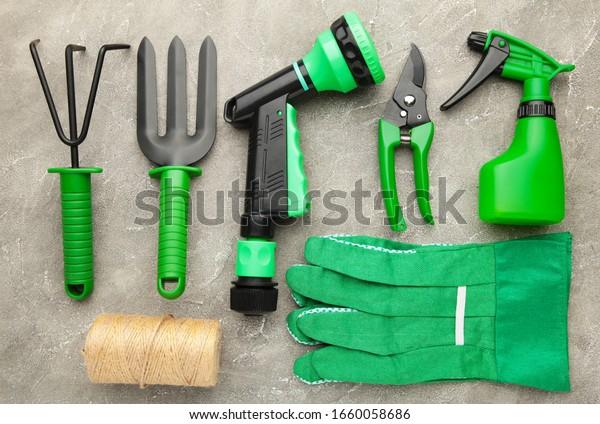 Gartenwerkzeuge auf grauem Betonhintergrund. Frühjahrskonzept