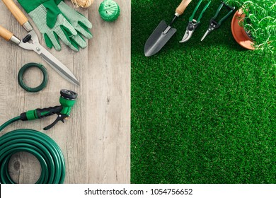 Gardening tools on a wooden table and lush grass, hobby and garden manteinance concept
