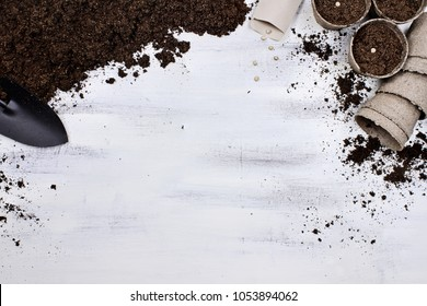 Gardening tools, seedling peat pots, seeds and soil on a white wooden table. Image shot from above in flat lay style.
