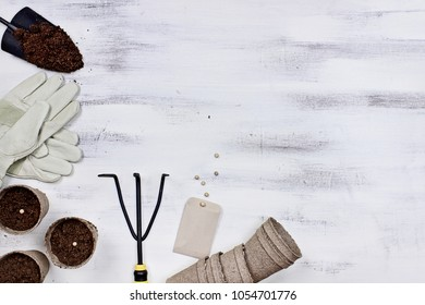 Gardening tools, seeds and soil on a white wooden table. Image shot from above in flat lay style.