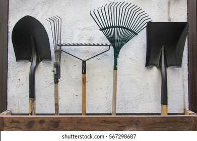 gardening tools, spade, fork and rake on cement wall ,garden tools concept.