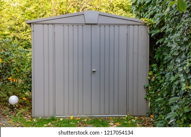 Gardening tools storage shed in the house backyard, autumn nature background