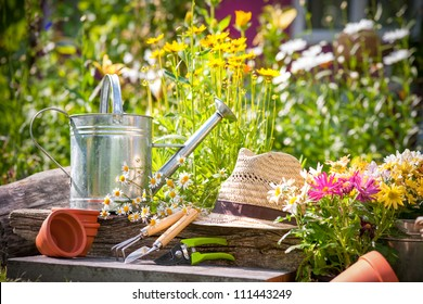 Gardening tools and straw hat on the grass in the garden