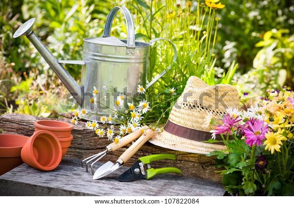 Gartenwerkzeug und Strohhut auf dem Gras im Garten