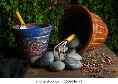 Gardening  utensils and pots with rocks on a rustic table ina low key light image or night photography