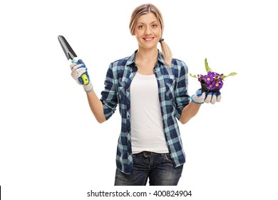 Gardening woman holding a spade and a flower in a pot isolated on white background