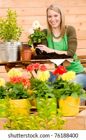 Gardening woman planting spring flower on terrace