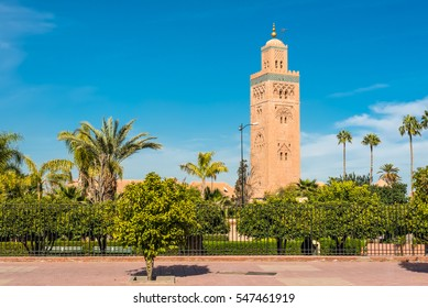 Gardens flank the Koutoubia Mosque (Kutubiyya Mosque) - the largest mosque in Marrakesh, Morocco. The minaret tower includes a secondary tower, a dome, a spire of four orbs, and a flag pole.
