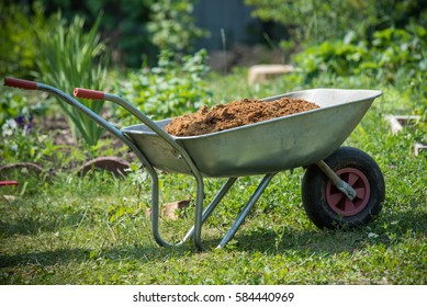 Garden-wheelbarrow filled with soil on a farm