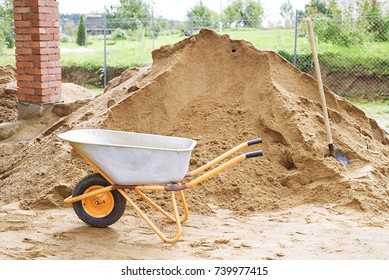 Garden-wheelbarrow with soil on a farm, barrow with loose soil and a square-point spade on the cultivated area in the autumn garden under reconstruction, one-wheeled wheelbarrow construction, Autumn