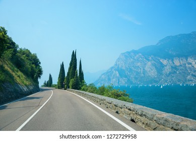 gardesana road along the west lakeside of garda lake, italy. Mediterranean landscape with pine trees. Sailboats on the lake.