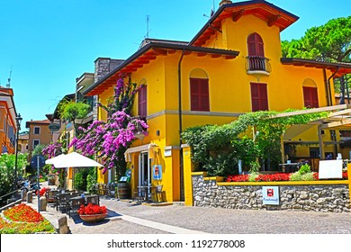 Gardone Riviera Lombardy Italy-July 19th 2018 Bright yellow traditional restaurant building at old nice decorated street