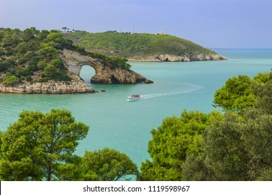 Gargano coast: San Felice arch (Architello), Italy.Gargano National Park,Vieste.The little rock arch is spectacular symbol of Vieste.Tourists on a boat visiting the coastline.