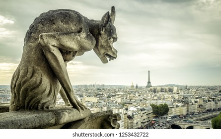 Gargoyle or chimera on the Cathedral of Notre Dame de Paris looks at the Eiffel Tower, Paris, France. Gargoyles are the Gothic landmarks in Paris. Vintage skyline of Paris with an old demon statue.