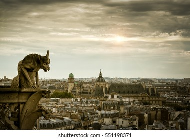 Gargoyle (chimera) on the Cathedral of Notre Dame overlooking Paris, France. Gargoyle on the dramatic sky background. Aerial panoramic view of Paris city with the old gargoyle. Mystic Paris skyline.