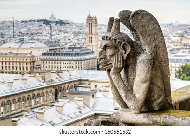 Gargoyle (chimera) on the Notre Dame de Paris cathedral overlooking Paris, France. Notre Dame is one of the main architecture landmarks in Paris. View of Paris from above with a demon statue close-up.