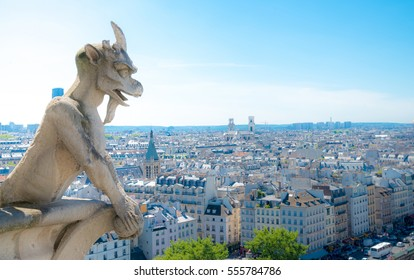 Gargoyle (chimera) on Notre Dame de Paris close up overlooking blur city at a summer day