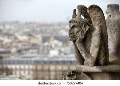 Gargoyle (chimera) on Notre Dame de Paris close up against a moody sky