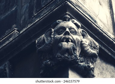 Gargoyle with protruding tongue. Architectural detail of old house in medieval town Arles (Provence, France). Toned photo.