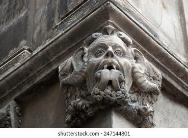Gargoyle with protruding tongue. Architectural detail of old house in medieval town Arles (Provence, France).