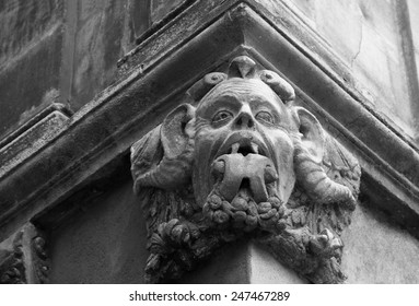 Gargoyle with protruding tongue. Architectural detail of old house in medieval town Arles (Provence, France). Aged photo. Black and white.