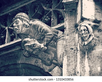 Gargoyle riding a goat and a witch head  on the facade of a building in the town hall yard of Munich  in Neo-Gothic style