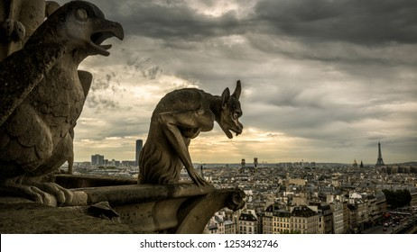 Gargoyles or chimeras on old Cathedral of Notre Dame de Paris overlooking city, France. Gargoyles are famous Gothic landmark of Paris. Dramatic skyline of Paris with vintage demon statue against sky.