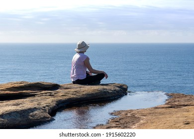 """""""Garie Beach NSW Australia 11th February 2021"""" Lady sitting next to Rock pool on coastal cliff along coastline walk in the Royal National Park NSW, overlooking the ocean"""