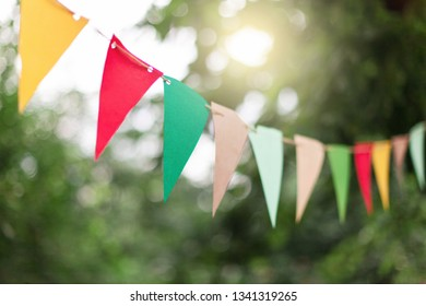 Garland of colorful flags at sunset in summer garden. Concept of celebration Happy Birthday party. Paper festive decoration outdoor.
