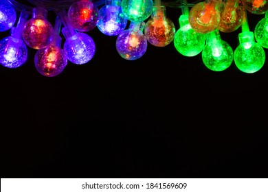 A garland of festive led lights hanging from top to bottom. Multi-colored Christmas lights close-up on a black background