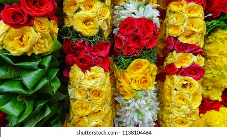 Garland with flowers of different colors are available for purchase in an Indian market