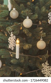 Garland in the form of candles on the Christmas tree. White decoration balls snowflakes on the Christmas tree close-up. Fake artificial Christmas tree