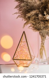 garland in a glass flask. candlestick garland in florarium glass geometric terrarium with reed flowers. reeds common bulrush in vase. dried flowers