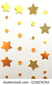 A garland of golden stars strung on a thread. Vertical image. Designer background for decoration in the room. Christmas wall decoration.