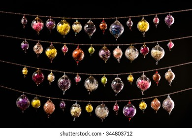Garland of hollow glass bubbles stuffed with flowers and other objects, isolated on black