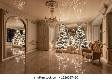 Garland light bulbs. Christmas evening. classic luxurious apartments with decorated christmas tree. Living hall large mirror, chair, high windows, columns and stucco.