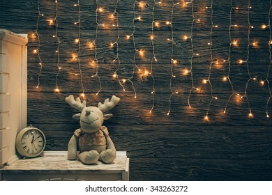 Garland Lights, toy deer, alarm clock on old grunge wooden board. Christmas and New Year decoration.  Christmas lighting on wooden planks
