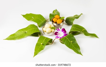 garland of mango leaves with indian sweet pedha and orchid flower . It is auspicious in hindu religion and used as a decoration during festivals in india.